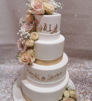 Bruidstaart met gouden accenten en verse bloemen