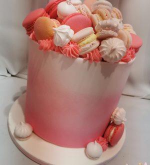 Over de top gedecoreerde cremetaart met macarons en meringes