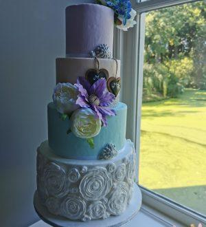 Pastelkleuren bruidstaart met rozenruffles