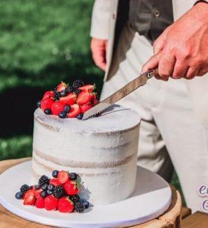 Aansnijmoment van de seminaked bruidstaart met vers fruit