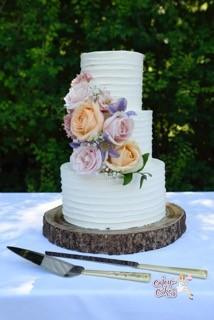 Creme bruidstaart met verse bloemen bij slot moermond