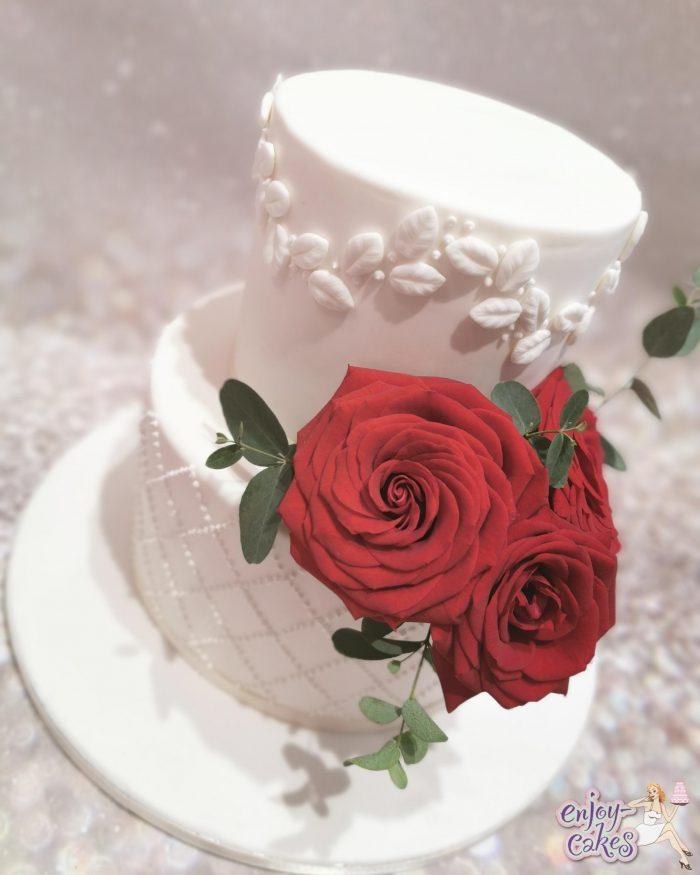 Witte bruidstaart met rode rozen